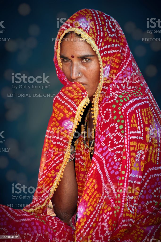 Portrait of an unidentified young Indian woman dressed in typical Rajasthani colorful and vibrant attire at Pushkar Camel Fair stock photo
