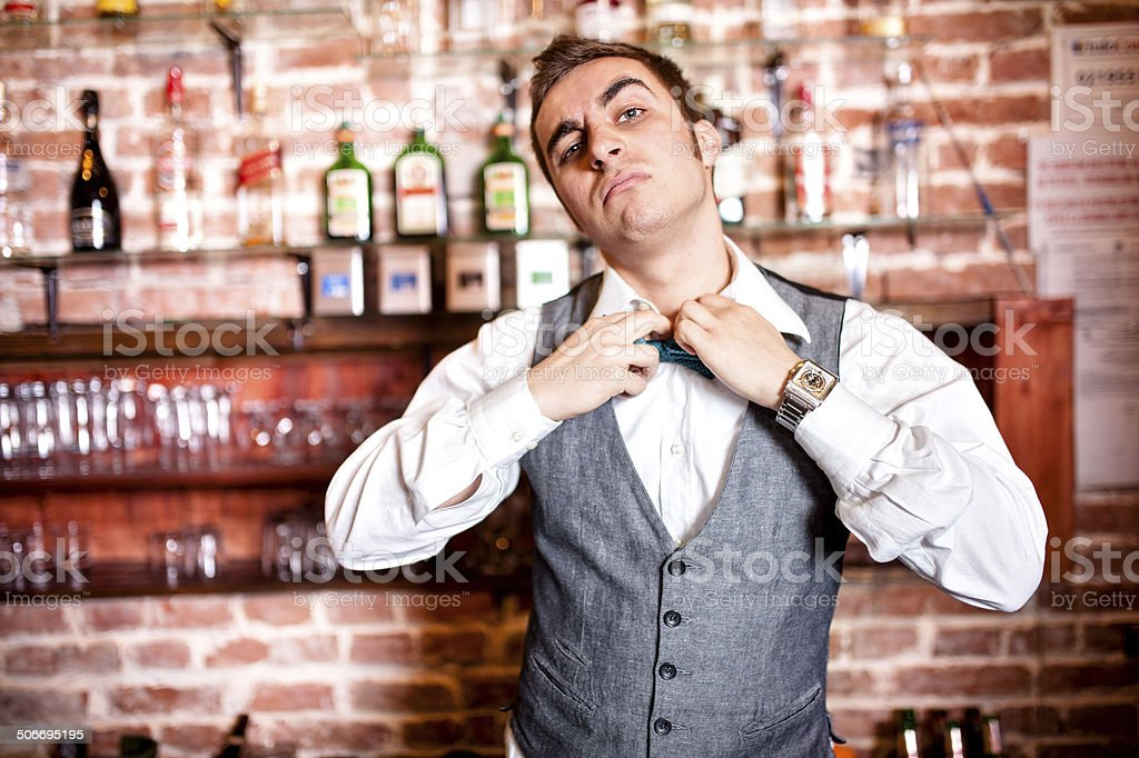 Portrait of angry and stressed barman with bowtie behind bar stock photo