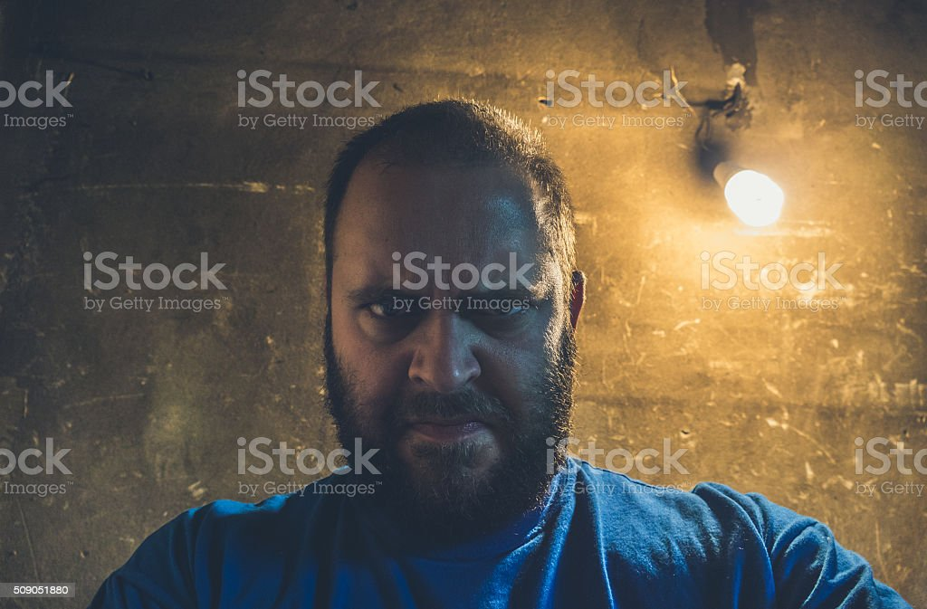 Portrait of angry man against damaged wall stock photo