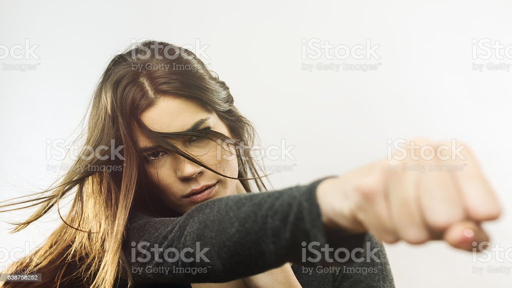 Portrait of angry woman punching the air stock photo