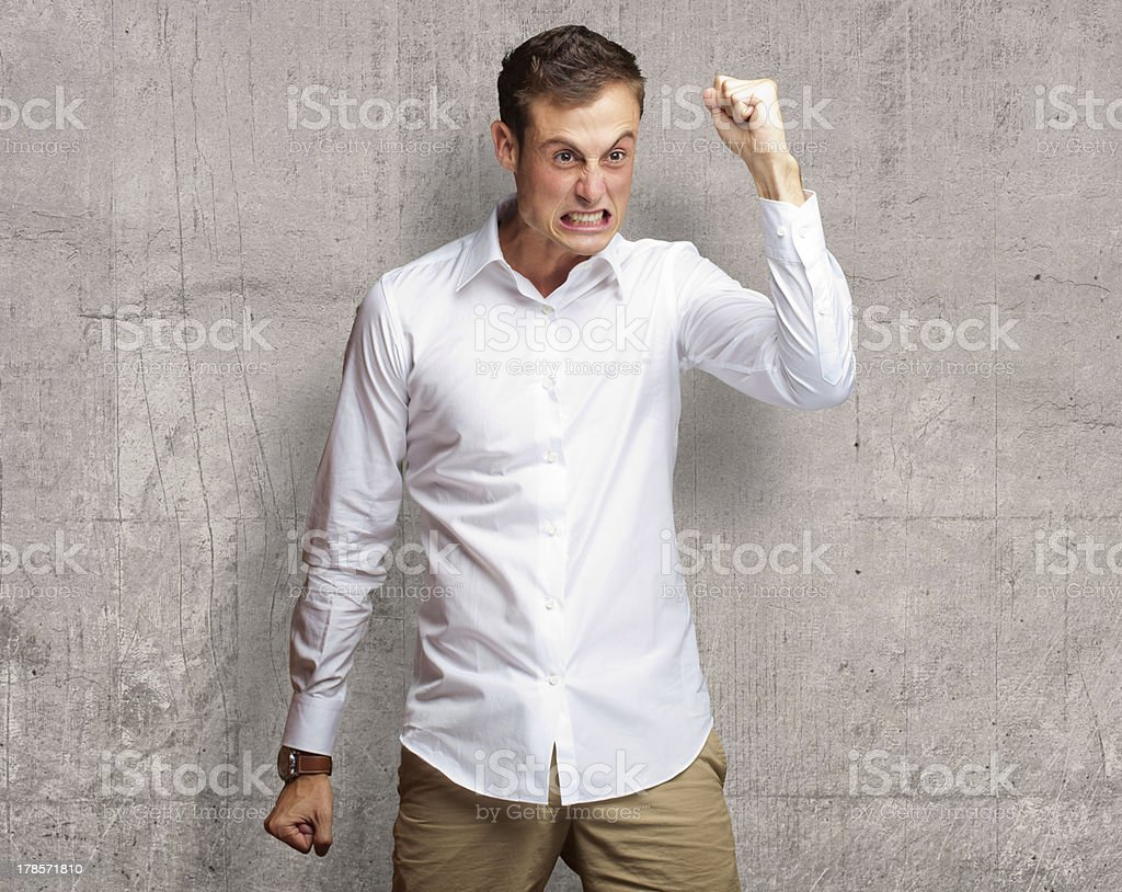 Portrait Of Angry Young Man Clenching His Fist stock photo