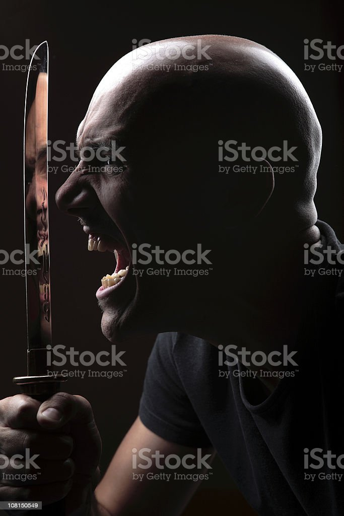 Portrait of Angry Young Man Holding Large Knife, Low Key royalty-free stock photo