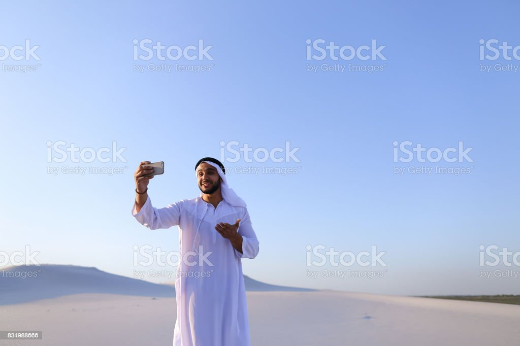 Portrait of Arabian sheikh man with gadget that communicates in stock photo