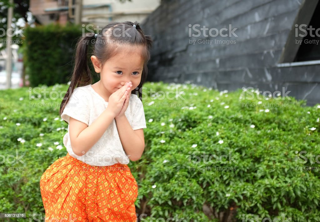 Portrait of asian child girl in traditional thai dress praying. stock photo