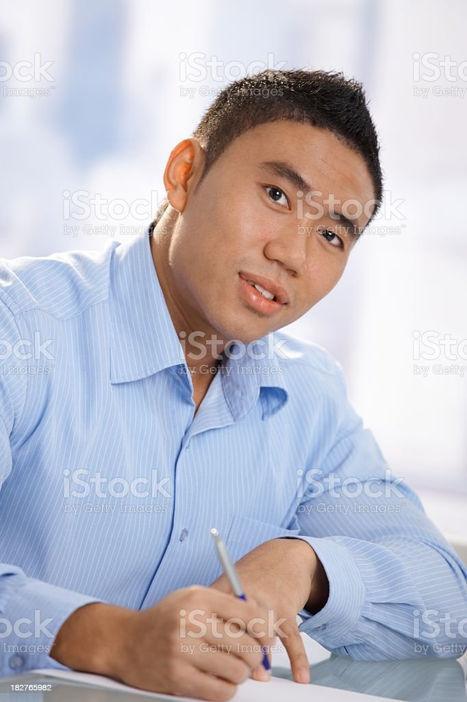 Portrait of asian man writing on desk royalty-free stock photo