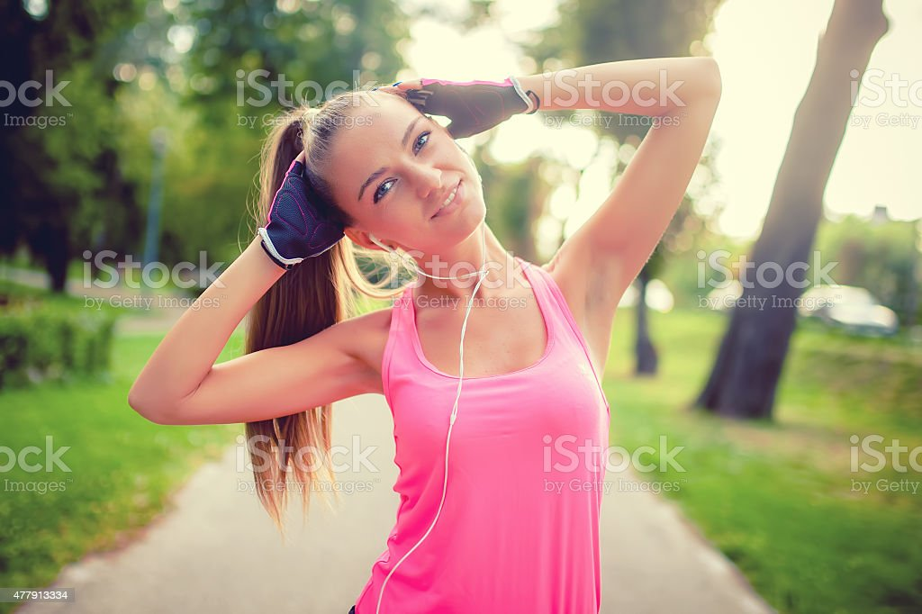 portrait of athletic girl working out and stretching in park stock photo