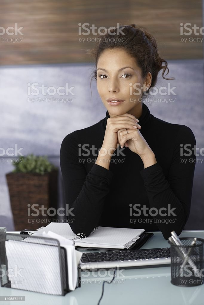 Portrait of attractive businesswoman at desk stock photo
