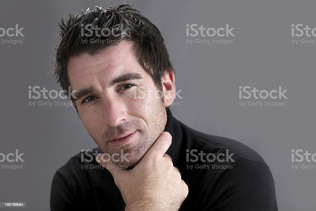 Portrait of attractive man in black with hand under chin stock photo