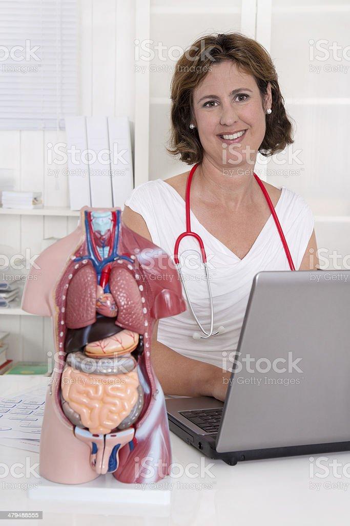 Portrait of attractive mature physician at desk. stock photo