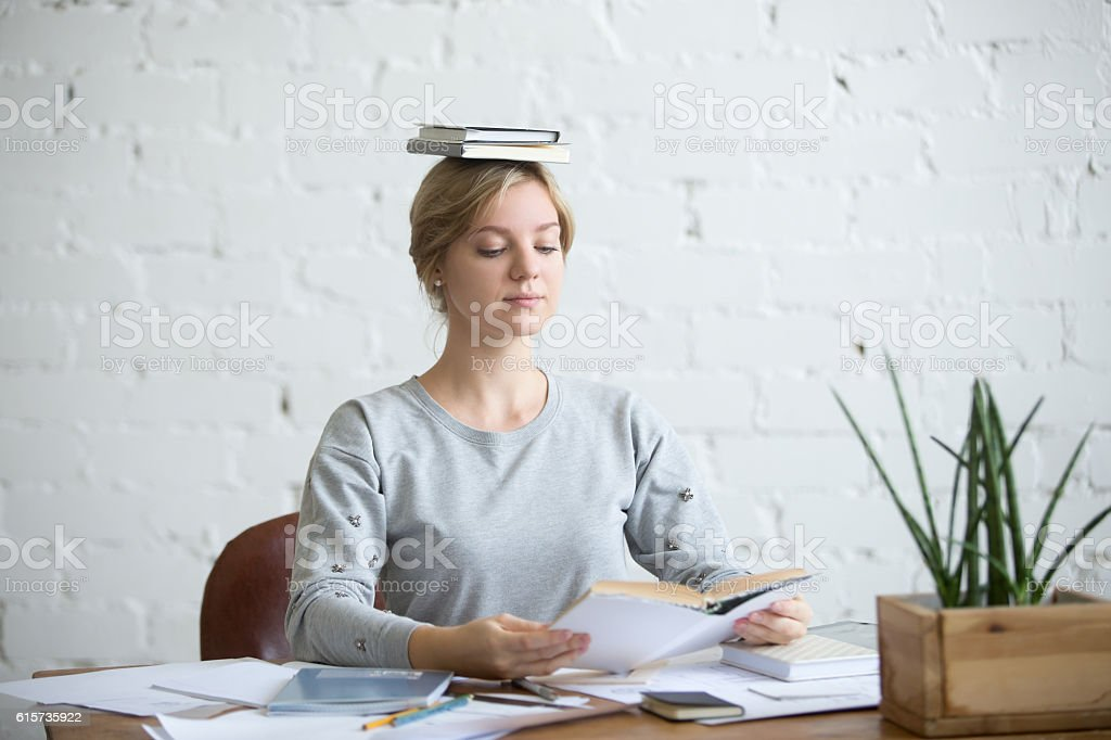 Portrait of attractive woman at desk, books on her head stock photo