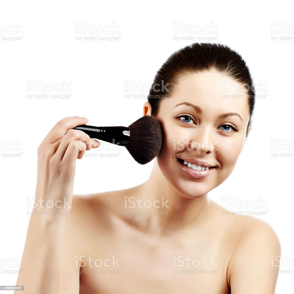 Portrait of attractive young adult woman applying blusher stock photo