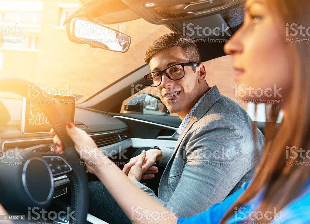 Portrait of attractive young couple driving black car in nature stock photo