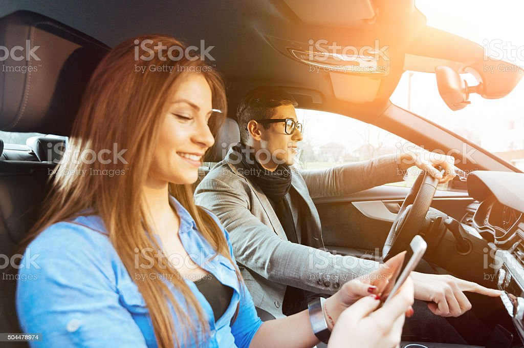 Portrait of attractive young couple driving luxury car in city stock photo