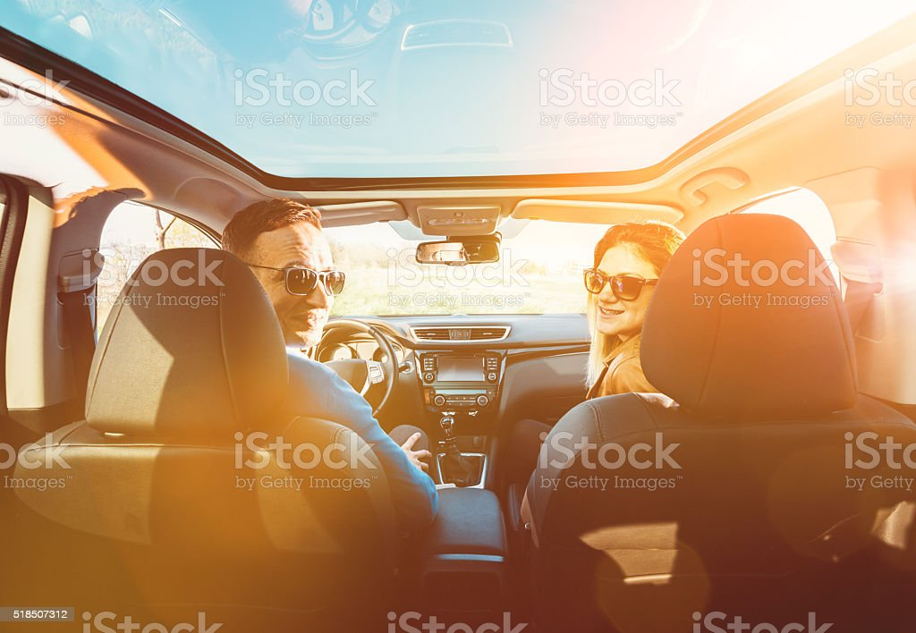 Portrait of attractive young couple driving luxury car in nature stock photo