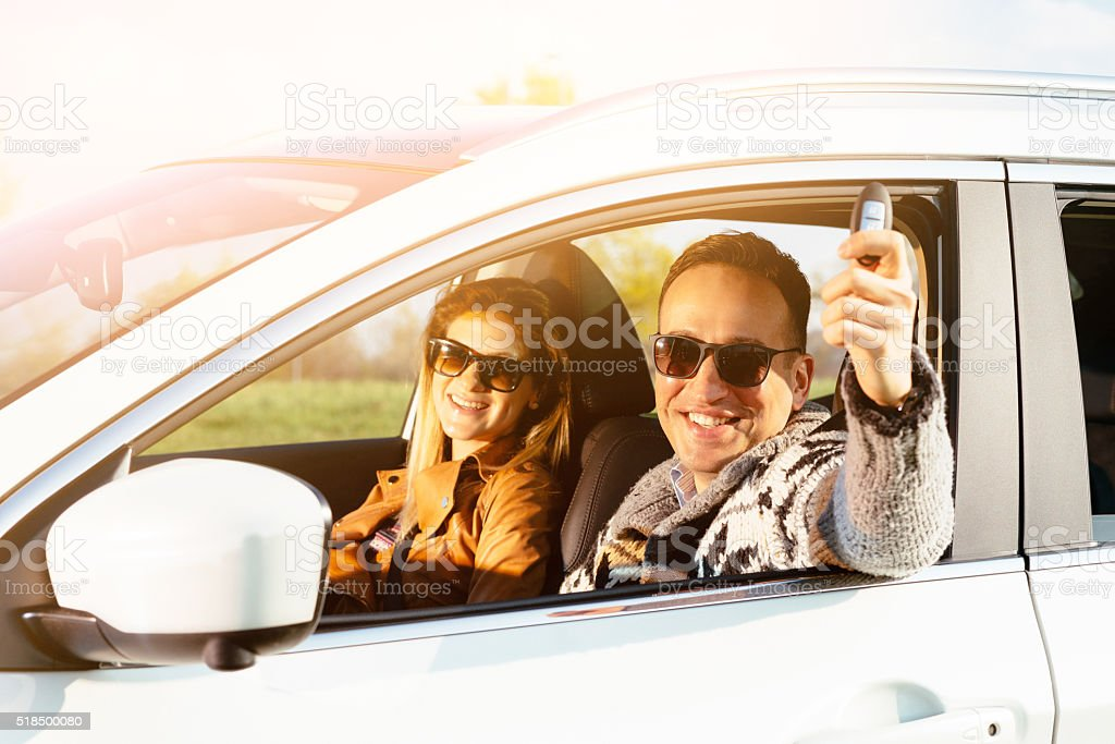 Portrait of attractive young couple in new car, showing keys stock photo