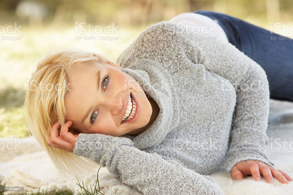 Portrait Of Attractive Young Woman Relaxing On Grass stock photo