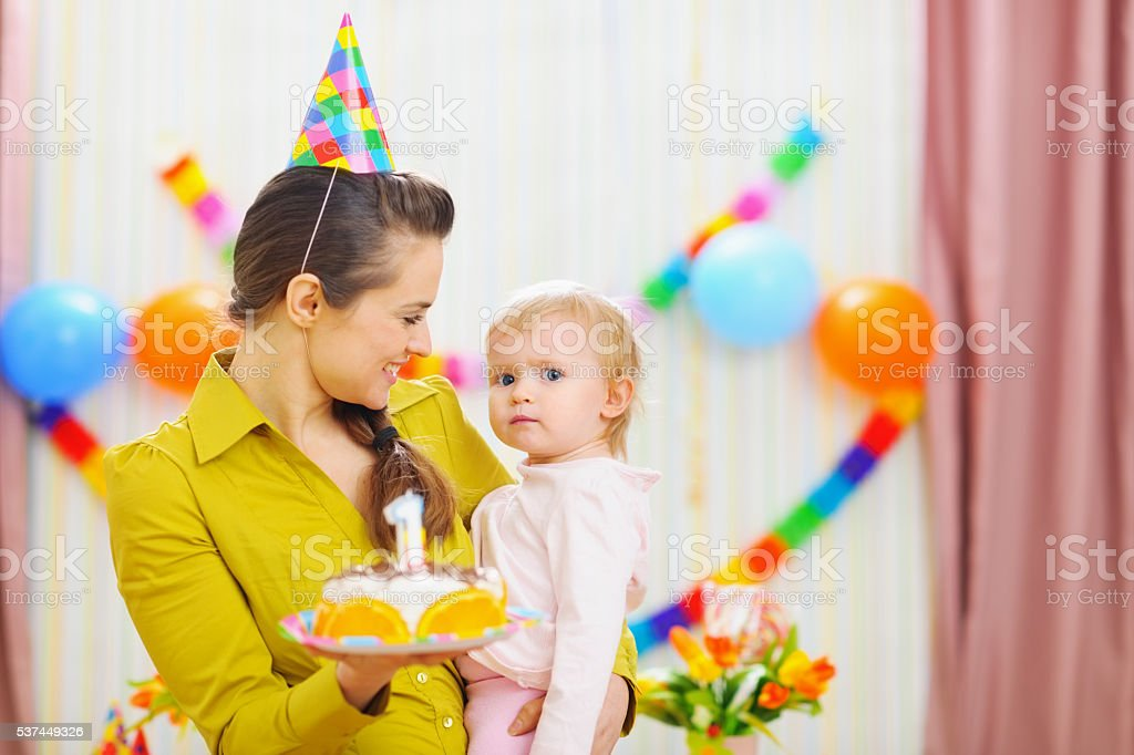 portrait of baby and mother with birthday party cake stock photo