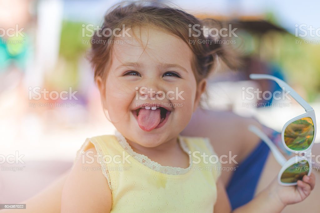portrait of baby girl with sunglasses on a beach stock photo