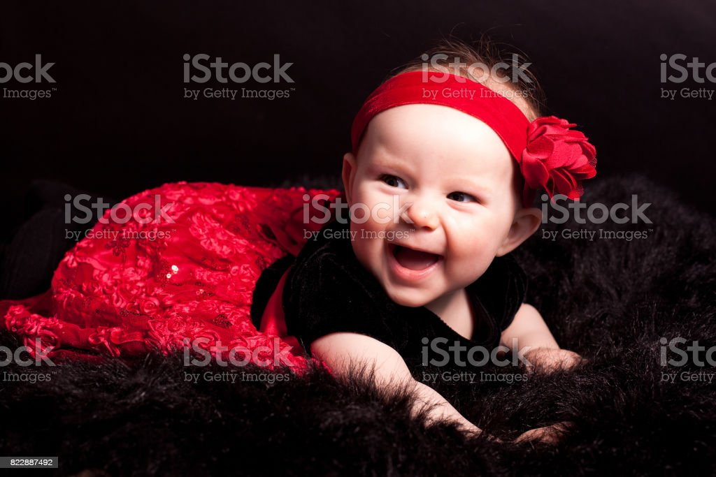 portrait of baby in red headband stock photo