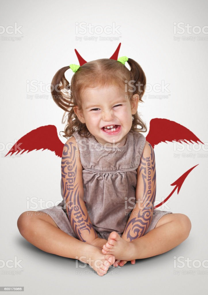 Portrait of bad child with tatoo and devil horns, disobedient baby concept stock photo