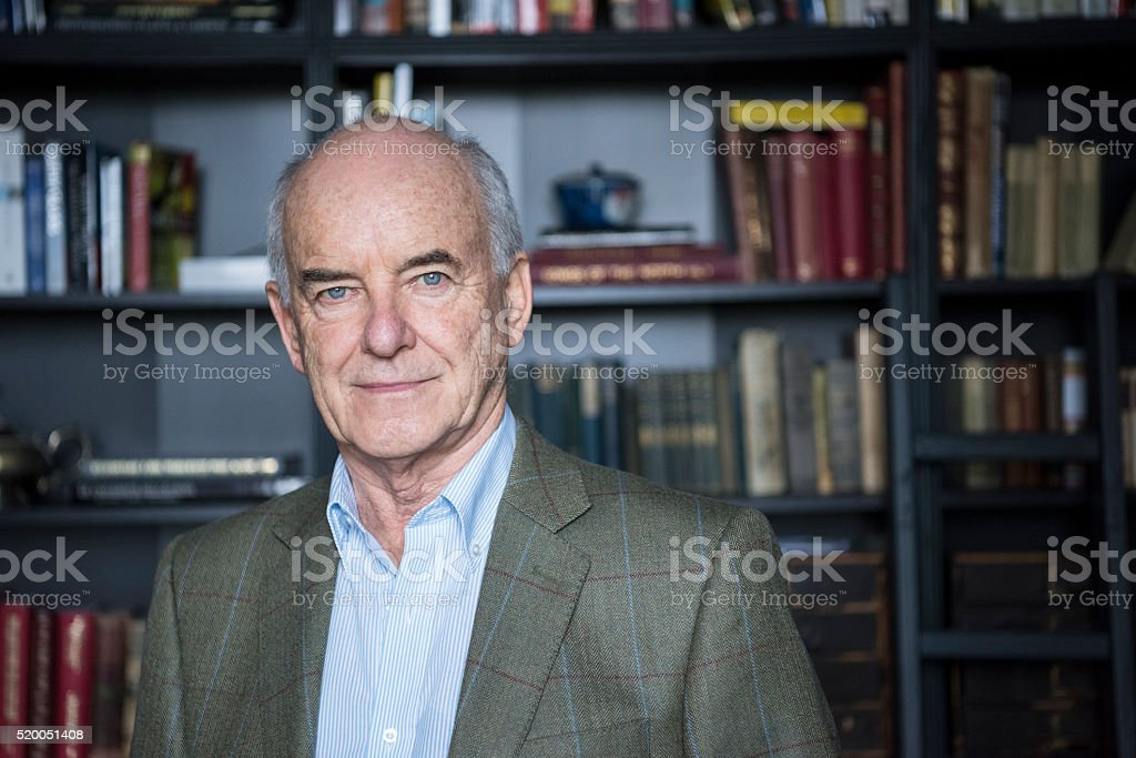 Portrait of balding senior man in front of bookcases stock photo