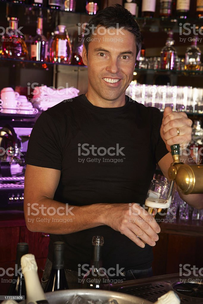 Portrait Of Barman Standing Behind Bar Pouring Beer royalty-free stock photo
