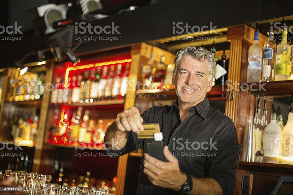 Portrait Of Bartender Swiping Credit Card Using Reader stock photo