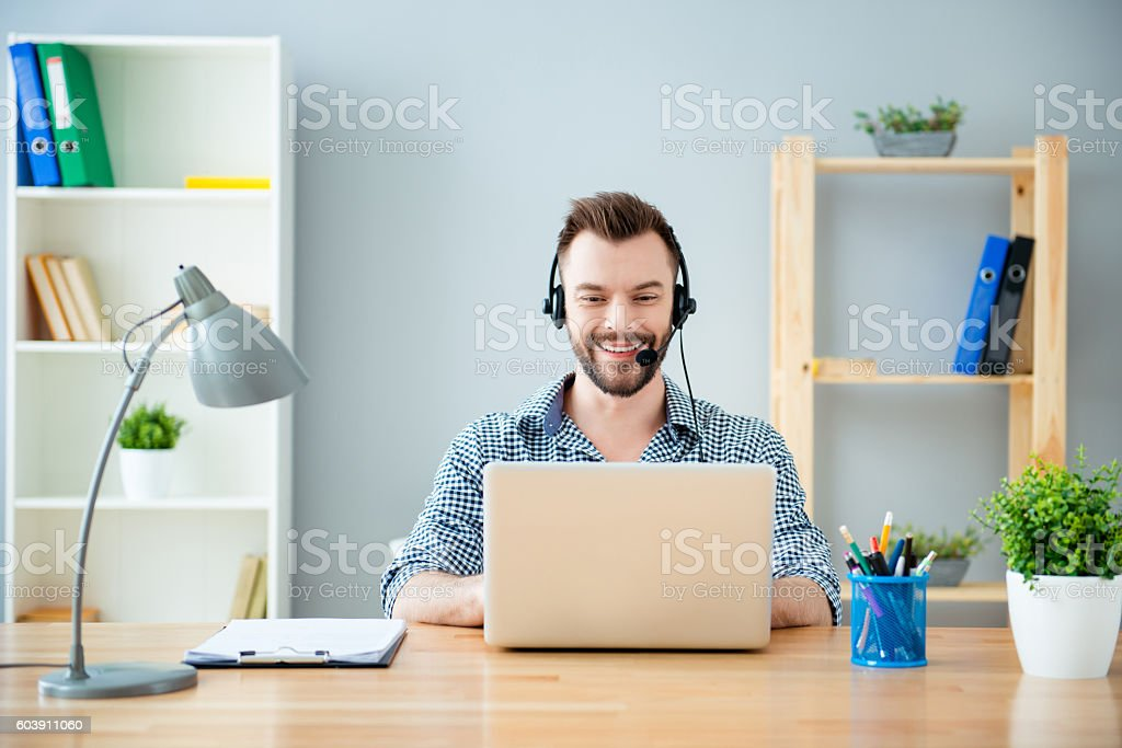 Portrait of bearded happy young worker of call center stock photo