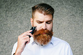 Portrait Of Bearded Man Trimming His Beard