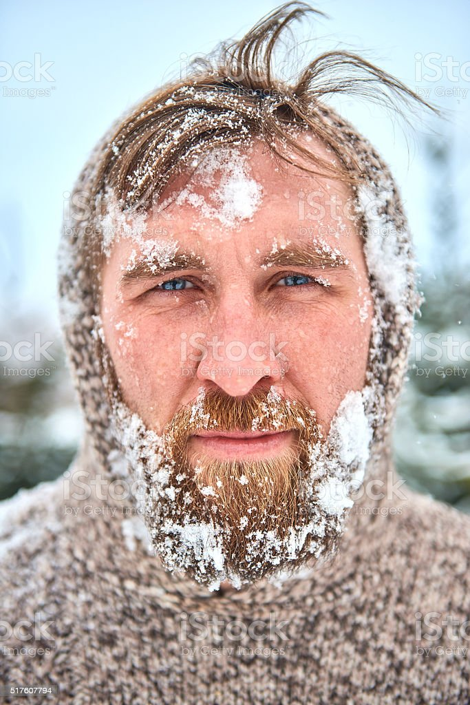 Portrait of bearded man with snow on his face stock photo
