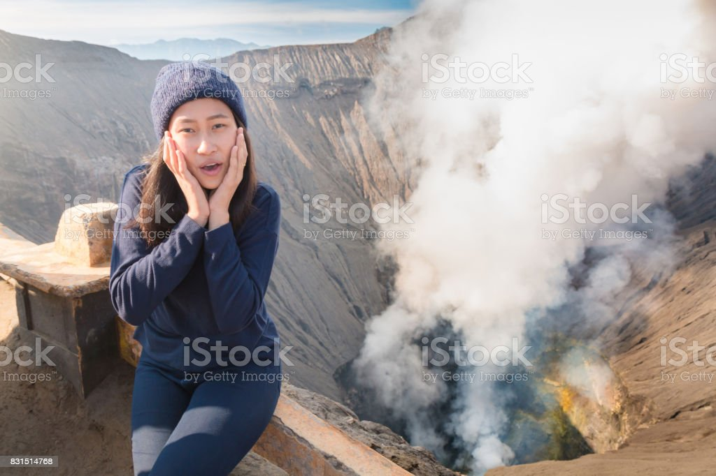 Portrait of beautiful asian woman smiles happily and sitting on volcano crater. Bromo Tengger Semeru National Park, East Java, Indonesia. stock photo