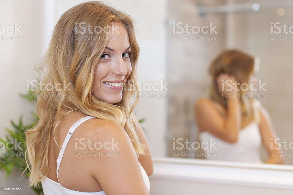 Portrait of beautiful blonde woman in bathroom stock photo