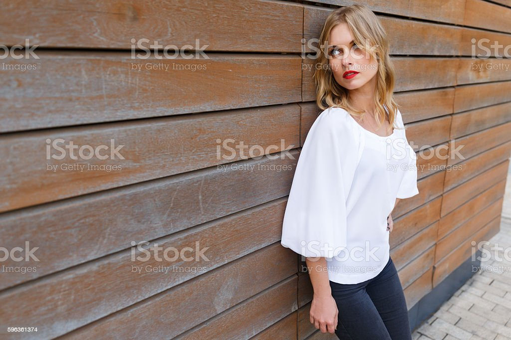 Portrait of beautiful blonde woman leaning on wall boards stock photo