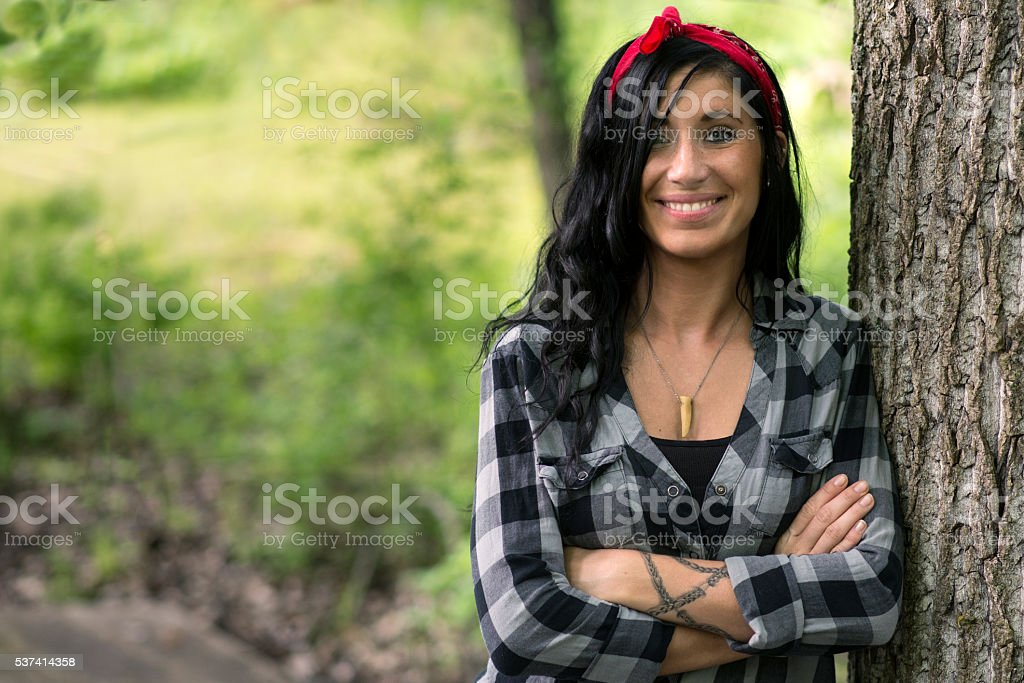 Portrait of Beautiful Brunette Woman Leaning Against Tree stock photo