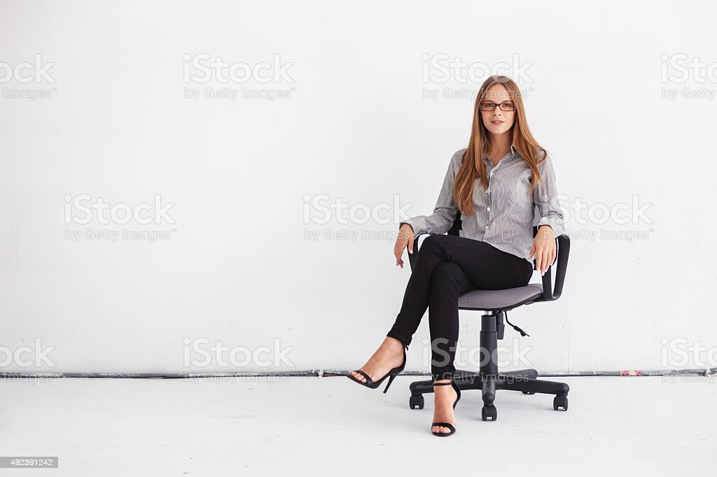 Portrait of beautiful business woman sitting on chair stock photo