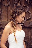 Portrait of beautiful fashion model as a bride posing outdoors