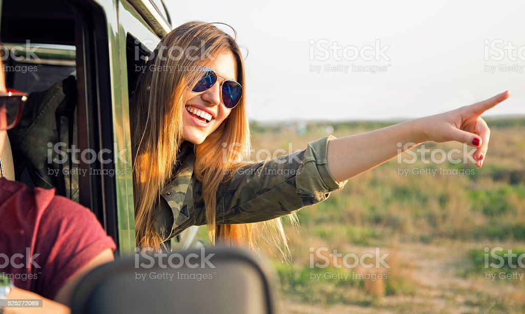 Portrait of beautiful girl on car roadtrip pointing forward. stock photo