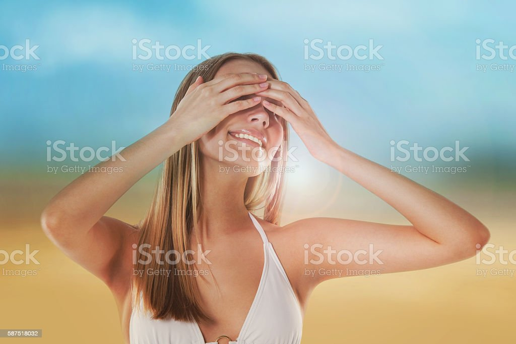 Portrait of beautiful girl on the beach hiding her eyes stock photo