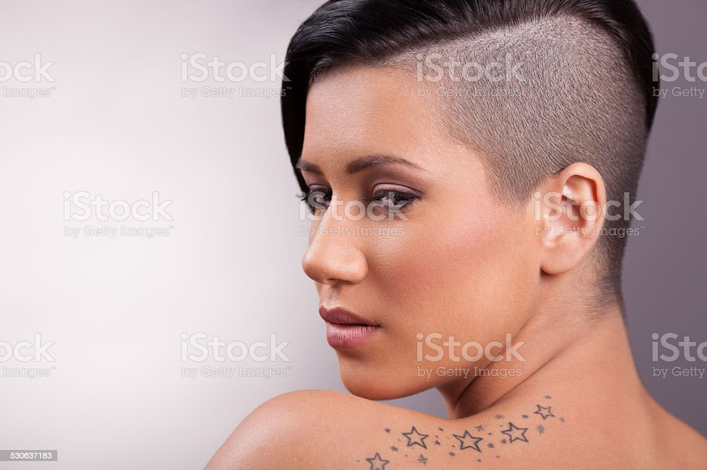 Beautiful young woman with unusual hairstyle. It has half the hair is...