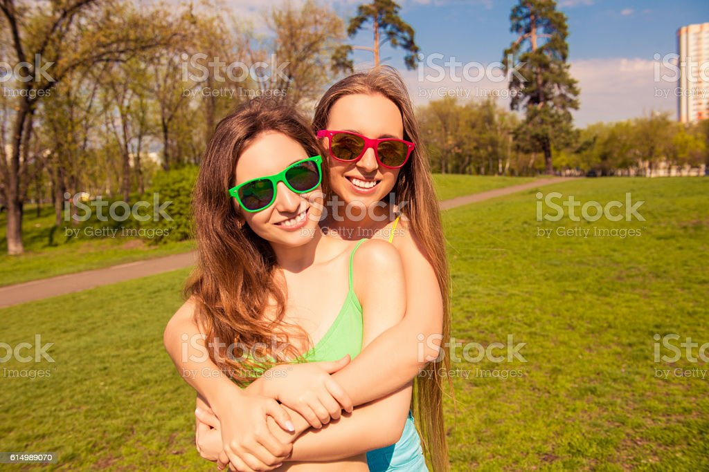 Portrait of beautiful girls in glasses embracing in the park stock photo