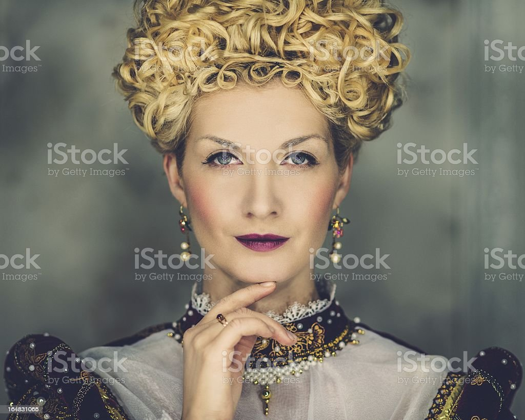 Portrait of beautiful haughty queen in royal dress stock photo