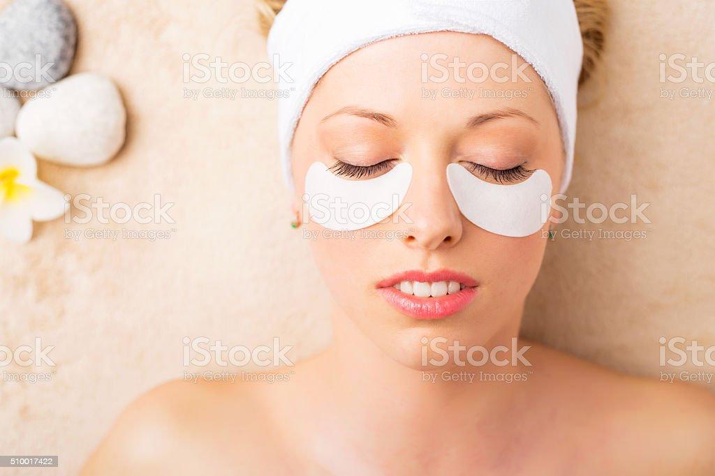 Portrait of beautiful healthy woman getting gel eye mask stock photo
