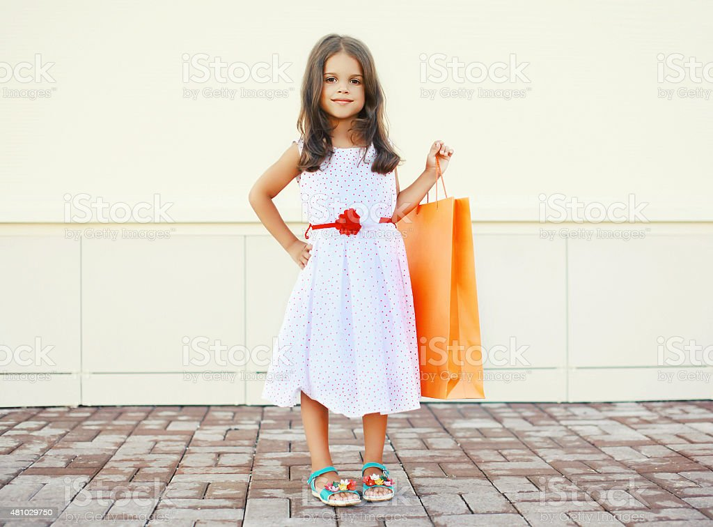 Portrait of beautiful little girl in dress and shopping bag stock photo