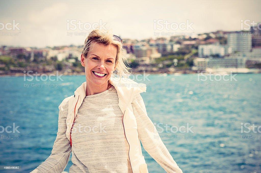 Portrait of beautiful mature woman, coastline on background stock photo