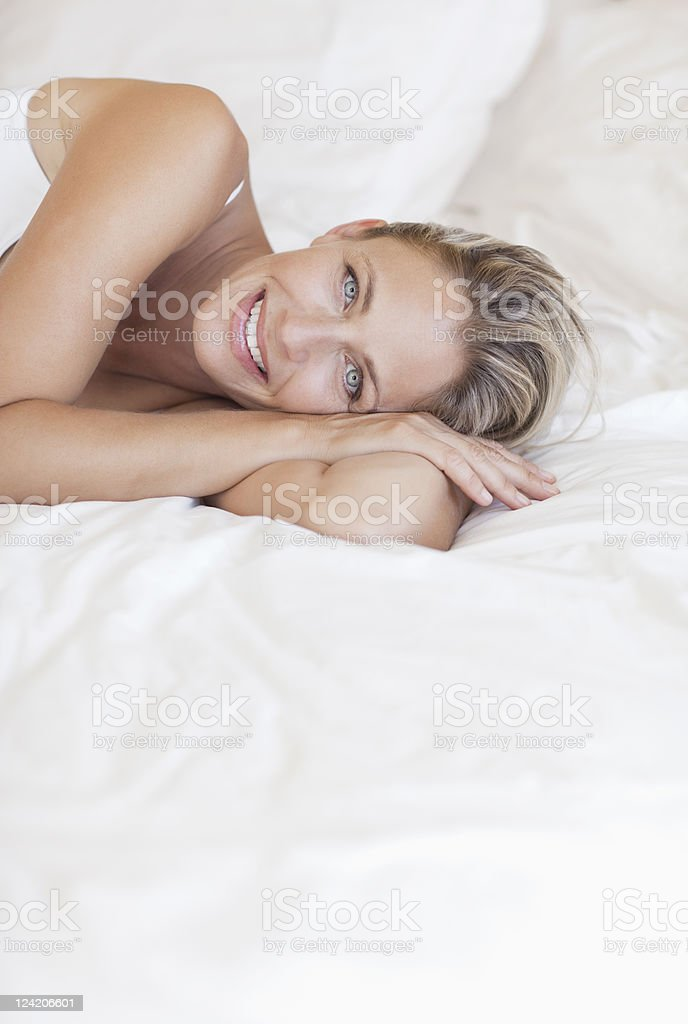 Portrait of beautiful mature woman lying in bed stock photo
