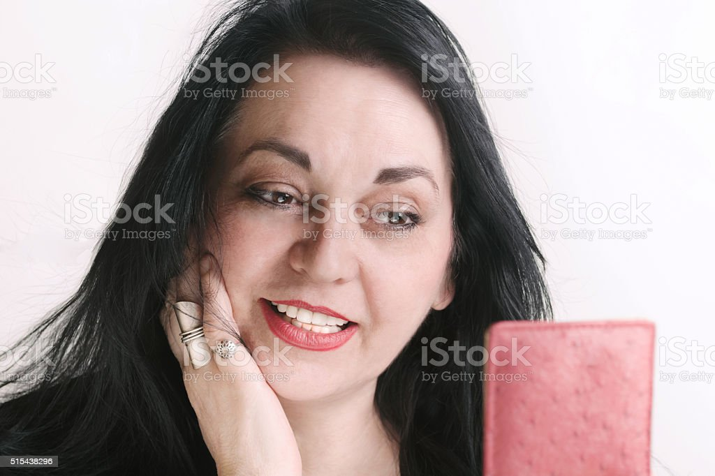 Portrait of Beautiful Mature Women Looking Herself in a Mirror stock photo