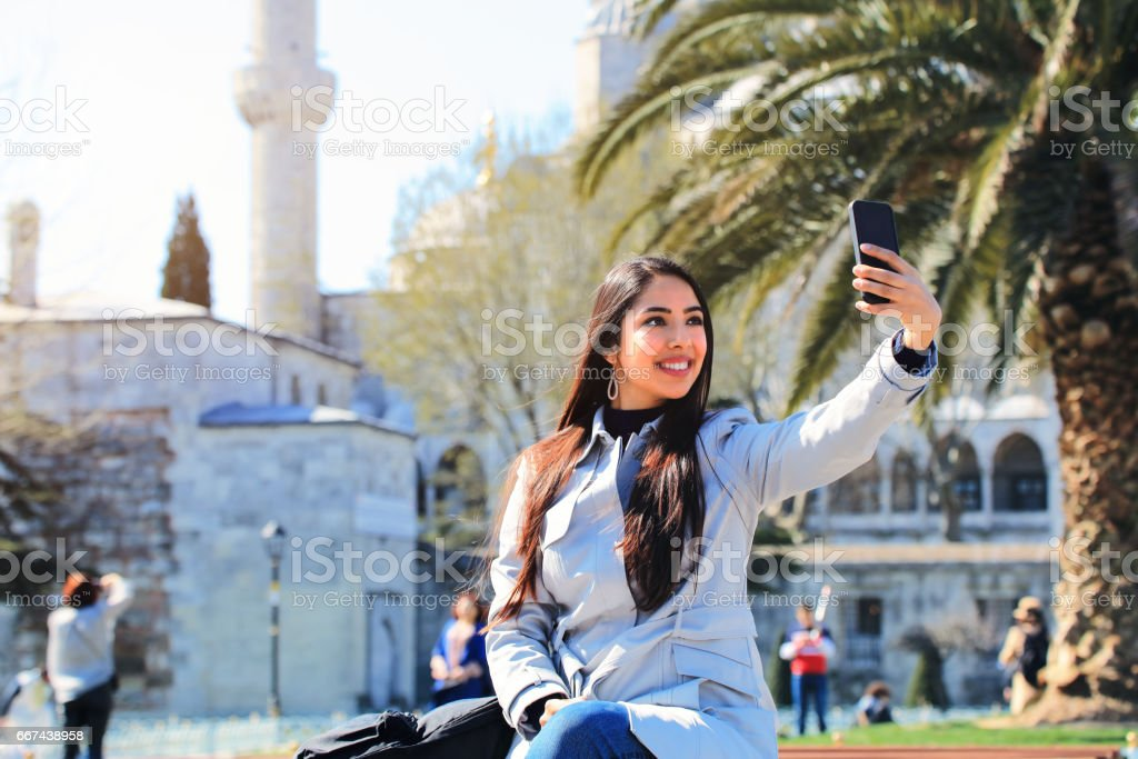 Portrait of beautiful muslim woman taking selfie with view of Blue Mosque, Sultanahmet District, Istanbul, Turkey stock photo