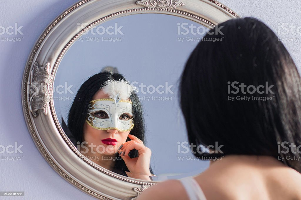 Portrait of beautiful mysterious young woman in carnival mask stock photo