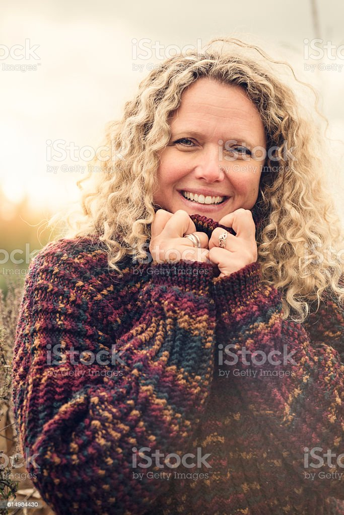 Portrait of beautiful real woman in corn field autumn sunset. stock photo