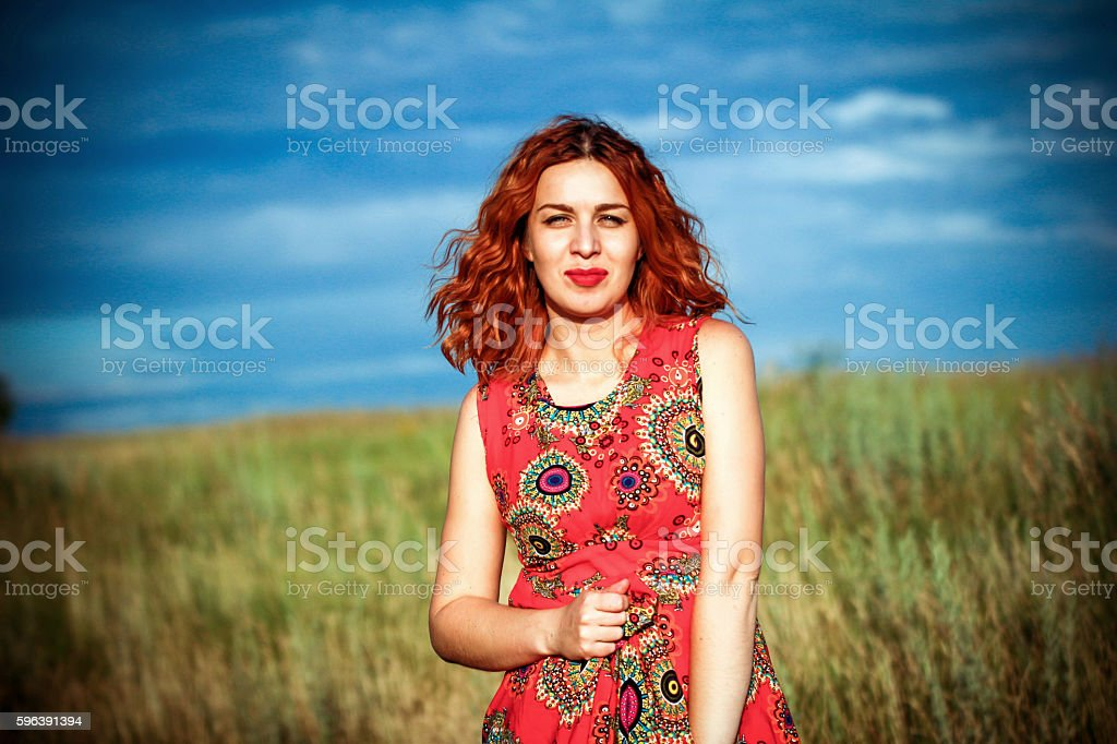 portrait of beautiful red-haired girl posing outdoors stock photo